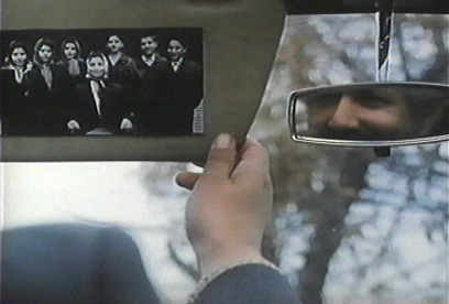 The taxi driver smiles at a photo of his family.